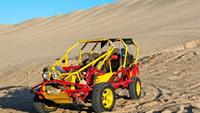 A yellow and red dune buggy or sand car on a large dune
